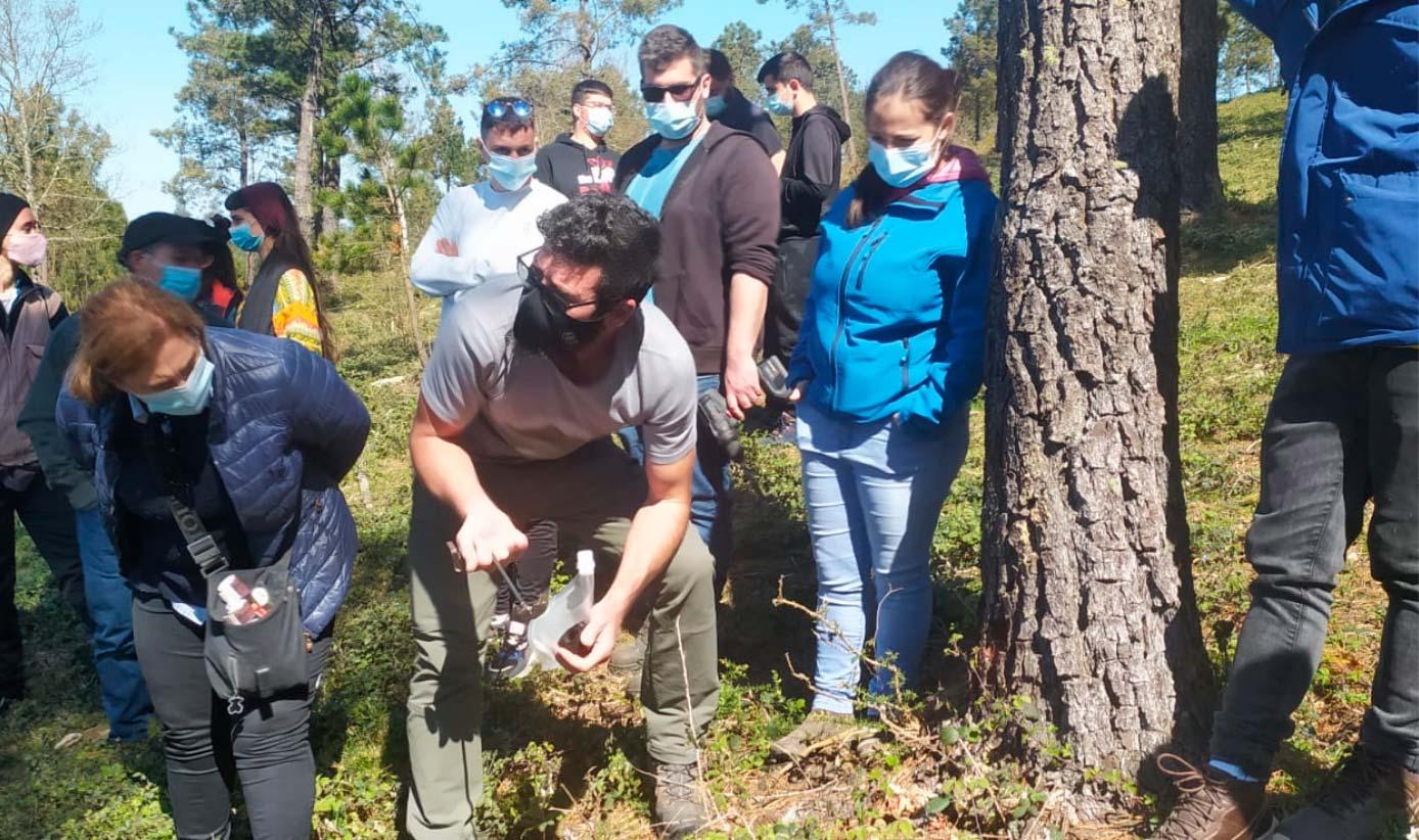 Grupo de gente en una plantación asistiendo a una jornada de formación.